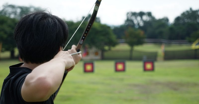 A person aiming a bow and arrow at a target